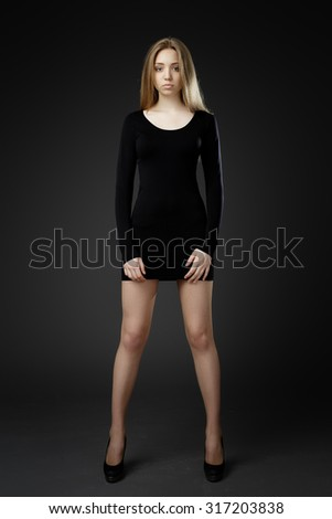 Full-length portrait young elegant woman in black dress. Fashion studio shot - stock photo