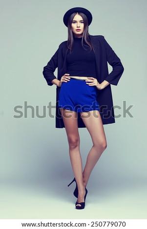 Full-length portrait young elegant woman in blue shorts, black jacket. Fashion studio shot  - stock photo