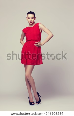 Full-length portrait young elegant woman in red dress, fashion studio shot  - stock photo