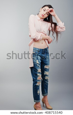 Full-length portrait young sexy brunette girl showing her navel, wearing in pink blouse, ripped jeans and cream shoes .Fashion studio shot - stock photo