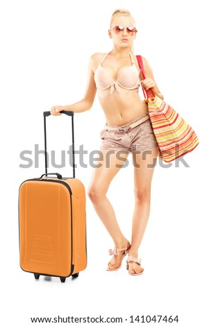 Full length portriat of a female tourist in bikini with a suitcase, isolated on white background