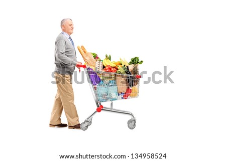 Full length potrait of a gentleman pushing a shopping cart full of groceries isolated on white background - stock photo