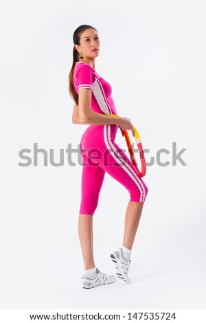 Full length potrait of young female athlete exercising with hula-hoop at white background - stock photo