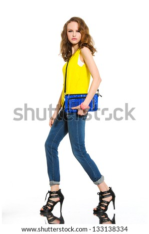 Full-length pretty young woman with bag posing in studio - stock photo