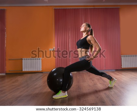 Full Length Profile of Serious Young Woman Wearing Exercise Clothing and Looking Upwards While Stretching Legs in Lunge Position and Next to Inflatable Exercise Ball in Dance Studio