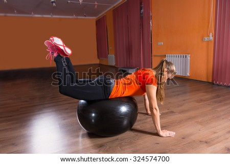 Full Length Profile of Young Blond Woman in Exercise Clothing Balancing on Inflatable Exercise Ball in Dance Studio with Hardwood Floor