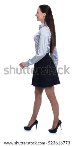 Full length profile portrait of a happy young woman walking against white background