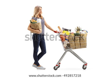 Full length profile shot a young woman waiting in line with a shopping cart and a paper bag isolated on white background