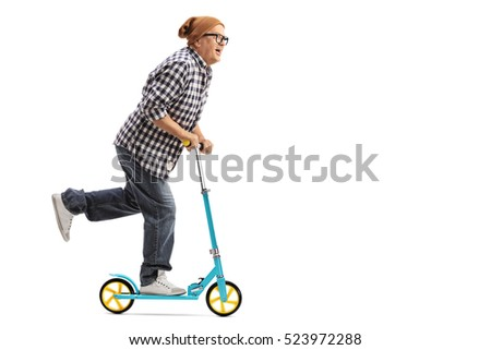 Full length profile shot of a cool mature man riding a scooter isolated on white background