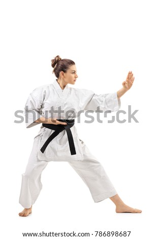 Full length profile shot of a karate girl doing a kata isolated on white background