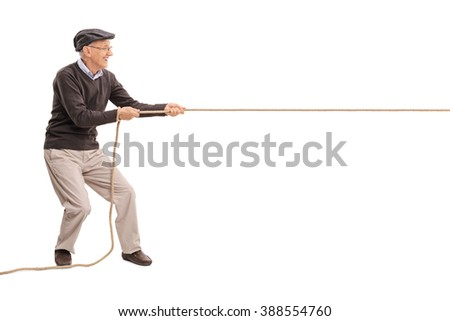 Full length profile shot of a senior gentleman pulling a rope isolated on white background - stock photo