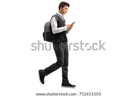 Full length profile shot of a teen student walking and using a phone isolated on white background