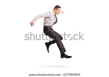Full length profile shot of a young businessman jumping in the air isolated on white background - stock photo