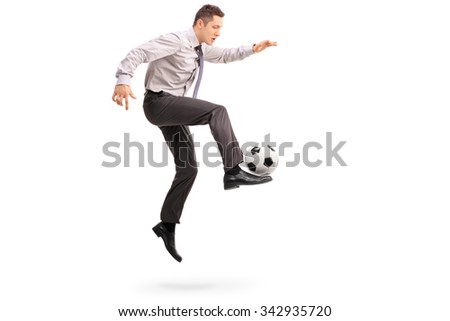Full length profile shot of a young businessman playing football shot in mid-air isolated on white background - stock photo