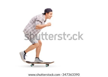 Full length profile shot of a young man riding a skateboard and smiling isolated on white background - stock photo
