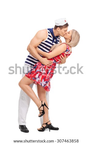 Full length profile shot of a young sailor kissing his girlfriend isolated on white background