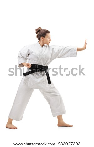 Full length profile shot of a young woman in a kimono practicing karate isolated on white background