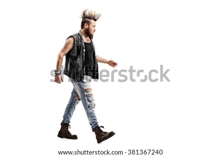 Full length profile shot of an angry male punk rocker walking isolated on white background - stock photo