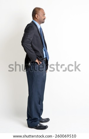 Full length profile view Indian businessman in formal suit looking at blank copy space, on plain background with shadow. - stock photo