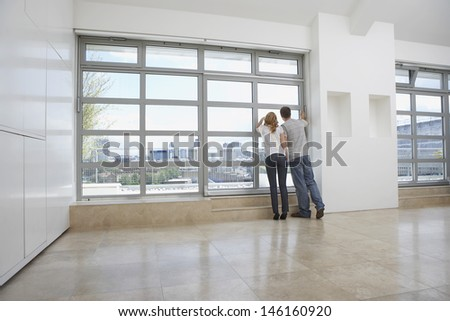 Full length rear view of a couple looking out of window in empty apartment - stock photo