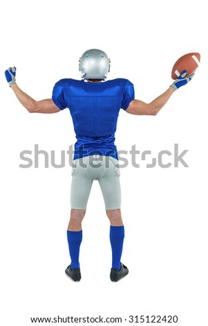 Full length rear view of American football player holding ball against white background - stock photo