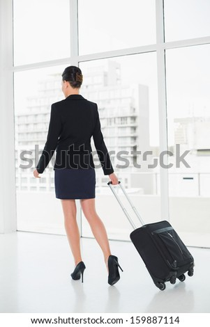Full length rear view of an elegant businesswoman in suit businesswoman pulling suitcase