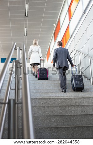 Full length rear view of businesspeople with luggage moving upstairs in railroad station - stock photo