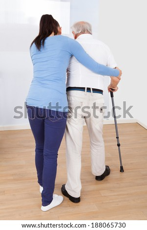 Full length rear view of caregiver assisting disabled senior man to walk with stick at nursing home