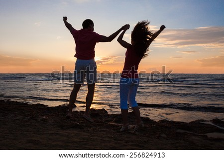 Full length rear view of couple enjoying ocean view at beach during sunset
