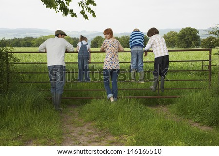 Full length rear view of couple with three children looking at lush landscape by fence