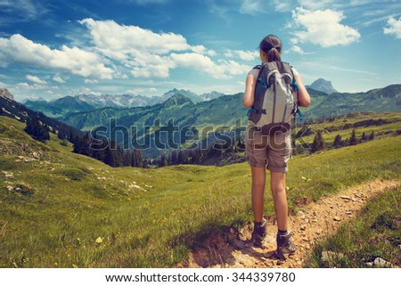 Full Length Rear View of Female Hiker Wearing Backpack Pausing on Trail to Admire View of Lush Green Mountain Valley on Bright Sunny Day - stock photo