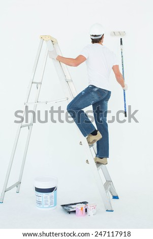 Full length rear view of man on ladder painting with roller over white background - stock photo