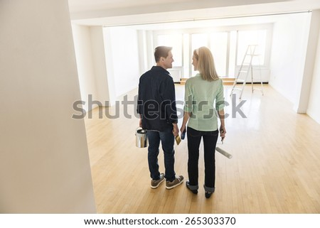 Full length rear view of mature couple with paint equipment standing at home - stock photo