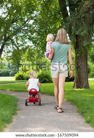 Full length rear view of mid adult mother with children strolling in park - stock photo