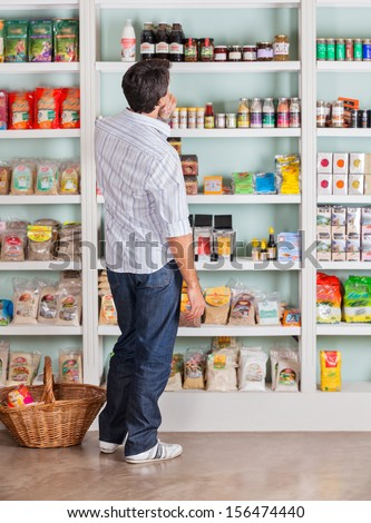 Full length rear view of thoughtful mid adult man looking at products in supermarket - stock photo