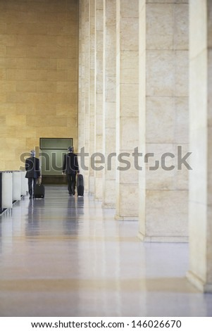 Full length rear view of two businessmen pulling luggage in airport lobby - stock photo