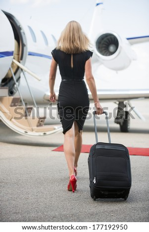 Full length rear view of wealthy woman with luggage walking towards private jet at airport terminal - stock photo