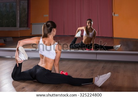 Full Length Rear View of Young Brunette Woman Stretching Legs in Splits Position and Looking at Reflection of Self in Mirrors in Dance Studio - stock photo
