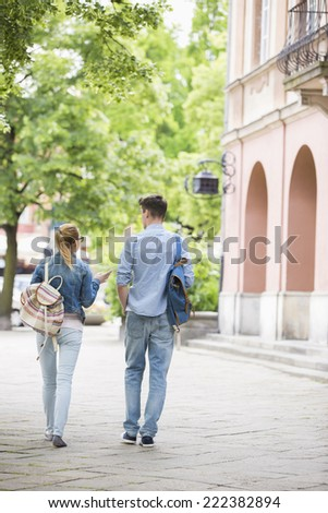 Full length rear view of young college friends talking while walking in campus - stock photo