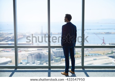 Full length rearview of a young stylish businessman standing at the large windows of a high office, looking at the view of a harbour below - stock photo