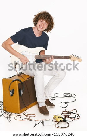 Full length redheaded male musician with his electric guitar sitting on the  guitar amplifier over white background - stock photo