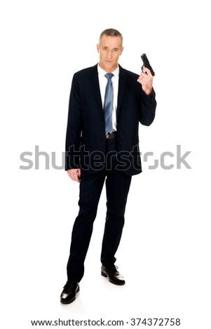Full length serious mafia agent with handgun - stock photo