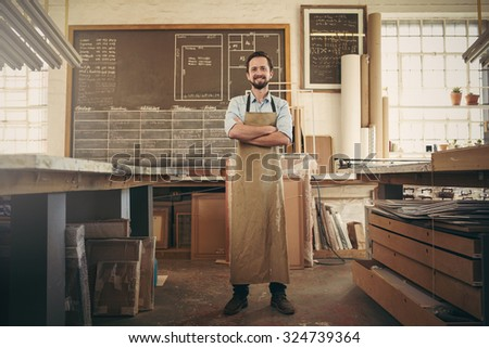 Full length shot of a craftsman standing confidently with his arms folded in the middle of his workshop studio smiling confidently at the camera - stock photo