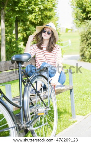 Full length shot of a dreaming young woman enjoying sunshine in the park while sitting on the bench.