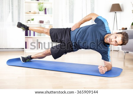 Full Length Shot of a Handsome Athletic Man Doing Side Plank Exercise with One Leg Raised, Looking at the Camera. - stock photo