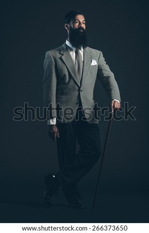 Full Length Shot of a Man with Long Beard Wearing Formal Suit Standing in Crossed Legs and Holding Cane While Looking to the Right of the Frame on a Black Background.