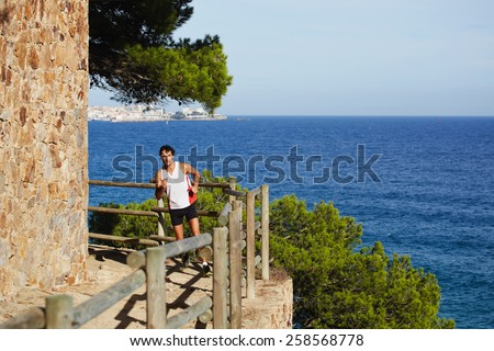 Full length shot of a sporty mature man running on the beach with beautiful sea on background, jogging athlete over mountain trail on high altitude - stock photo