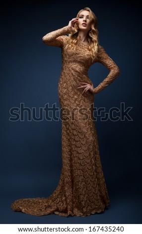 Full-length shot of a woman in golden dress - stock photo