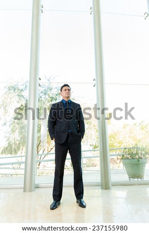 Full length shot of a young businessman standing inside a tall building - stock photo