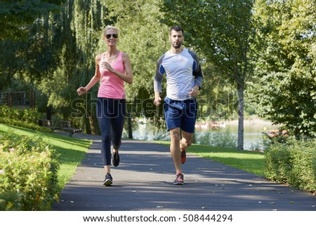 Full length shot of a young couple running together outdoors.